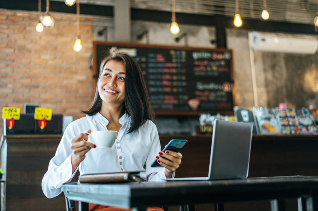 Woman Sitting Happily Working With A Smartphone In A Coffee Shop - Pontual Contadores & Associados